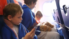 Family wrapped in counterpane sitting on board of the airplane Stock Footage
