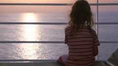 Girl sits on deck of cruise ship Stock Footage