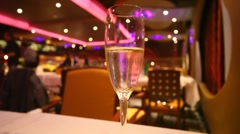 Rising up bubbles of champagne in glass against lights Stock Footage