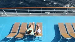 Woman and girl are lying on the deck chairs Stock Footage