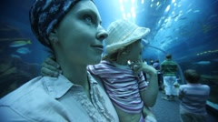 Woman holding daughter in oceanarium Stock Footage