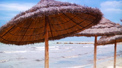 Thatched beach umbrellas in Tunisia Stock Footage