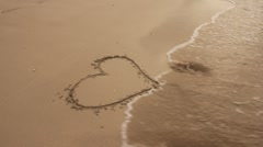 Waves wash away heart in sand (HD) k Stock Footage