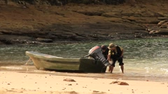Three people get ready to drag boat into water (HD) k Stock Footage