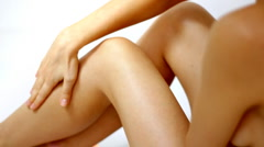 Woman gently touching her leg, isolated on white Stock Footage