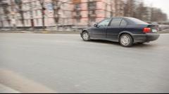 High quality tracking shot car make in U-turn, city street Stock Footage