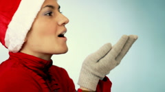 Woman in santa cap blowing white particles Stock Footage