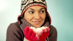 Attractive happy woman in woolen cap holding snow in her hands  Stock Footage