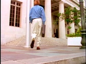 Stock Video Footage of Man walking toward courthouse steps.