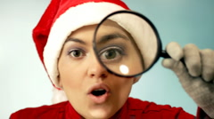 Woman in santa cap with magnifying glass  Stock Footage