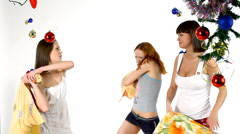 Girls stand and fight with pillow - new year scene Stock Footage