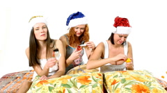 Young girls in santa hat eat chocolate on pillows - christmas theme Stock Footage