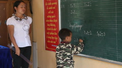 Little Asian Boy at Writes on Blackboard Teacher Vietnam Learning to Read Write  Stock Footage