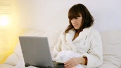 Young woman working with computer in the bed  Stock Footage