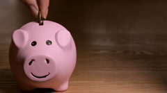Loop of dropping quarters into piggy bank - stock footage