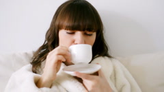 Attractive woman in bathrobe drinking coffee  Stock Footage