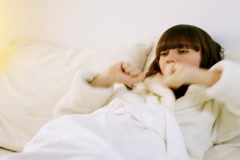 Attractive woman in bathrobe stretching in bed  Stock Footage