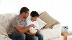 Father and son watching televison on the sofa Stock Footage