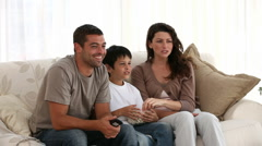 Family watching television on the sofa - stock footage