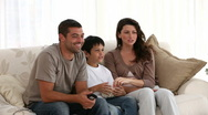 Family watching television on the sofa Stock Footage
