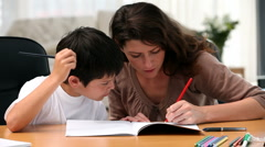 Mom doing homework with her son - stock footage