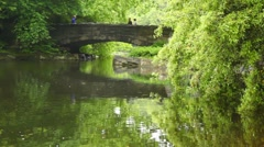 park with river and greenery people are going on  stone bridge - stock footage