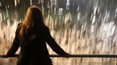 Back view of woman standing near railing and looks at artificial waterfall Stock Footage