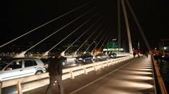 Cars stoped, people walks on night Samuel Beckett Bridge Stock Footage