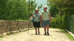 Stock Video Footage of Elderly married couple walking on cobbled road 4