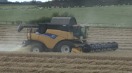 Stock Video Footage of New Holland combine harvester at work on wheat.
