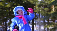 Little girl walking outdoor in the winter pine forest Stock Footage