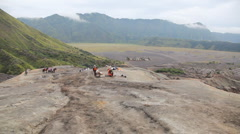 Indonesian people and horses between volcanos Batok and Bromo Stock Footage