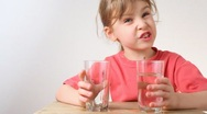 Stock Video Footage of little girl pouring water from one glass to another