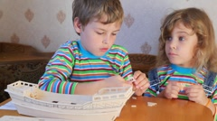 Sitting boy and girl constructing toy model of ship Stock Footage