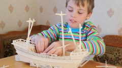 Boy constructing toy model of ship Stock Footage