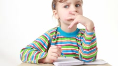 Puzzled girl sitting at table with pencil and notebook Stock Footage