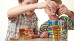 Boy and little girl stiring and drink juice Stock Footage