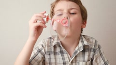 Boy sitting and blowing huge soap bubble Stock Footage
