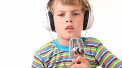 Boy in earphones talking through microphone Stock Footage
