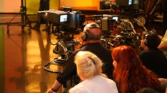 Back view of cameramans and spectators in big TV studio during filming Stock Footage
