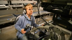 Boy operating stationary camera in big TV studio with spectators Stock Footage