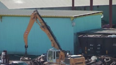 Crane shifting scrap metal in junkyard  - stock footage