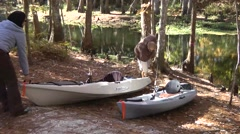 Kayaking couple ready to launch craft from river bank - stock footage