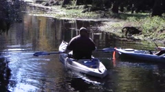 Kayaking couple paddle gently downstream - stock footage
