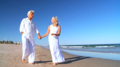 Seniors Walking Barefoot on the Beach Stock Footage