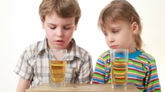 Boy and girl sitting and drink juice Stock Footage