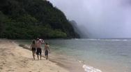 Kauai a family walks down beach Stock Footage