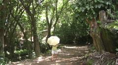 Hawaii Kauai Man with an umbrella walks on a path Stock Footage