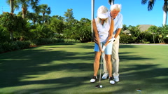 Mature Lady Learning to Play Golf Stock Footage
