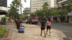 Waikiki pedestrians and pink trolley  Stock Footage